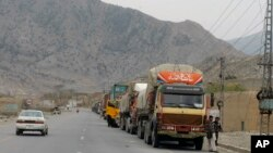 Truck drivers stand beside their trucks while they waiting for border opening at a highway leading to Torkhum