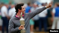 Rory McIlroy of Northern Ireland celebrates as he holds the Claret Jug after winning the British Open Championship at the Royal Liverpool Golf Club in Hoylake, northern England July 20, 2014. REUTERS/Cathal McNaughton (BRITAIN - Tags: SPORT GOLF) -