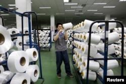 FILE - An employee works inside a textile mill in Yiwu, Zhejiang province.