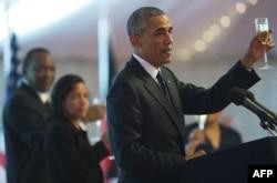 President Barack Obama raises a toast during a state dinner hosted by Kenyan President Uhuru Kenyatta, left, at the State House in Nairobi, July 25, 2015.