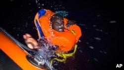 Un migrant nage vers un navire de sauvetage au large des côtes libyennes, dans la nuit du 2 août 2018.