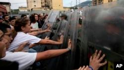 Los estudiantes universitarios empujan los escudos antidisturbios de los oficiales de la Guardia Nacional Bolivariana Venezolana durante una protesta fuera del Tribunal Supremo en Caracas, Venezuela, el viernes 31 de marzo de 2017.