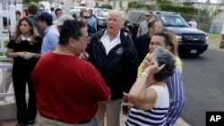 President Donald Trump talks to residents while taking a walking tour to survey hurricane damage and recovery efforts in a neighborhood in Guaynabo, Puerto Rico, Oct. 3, 2017.