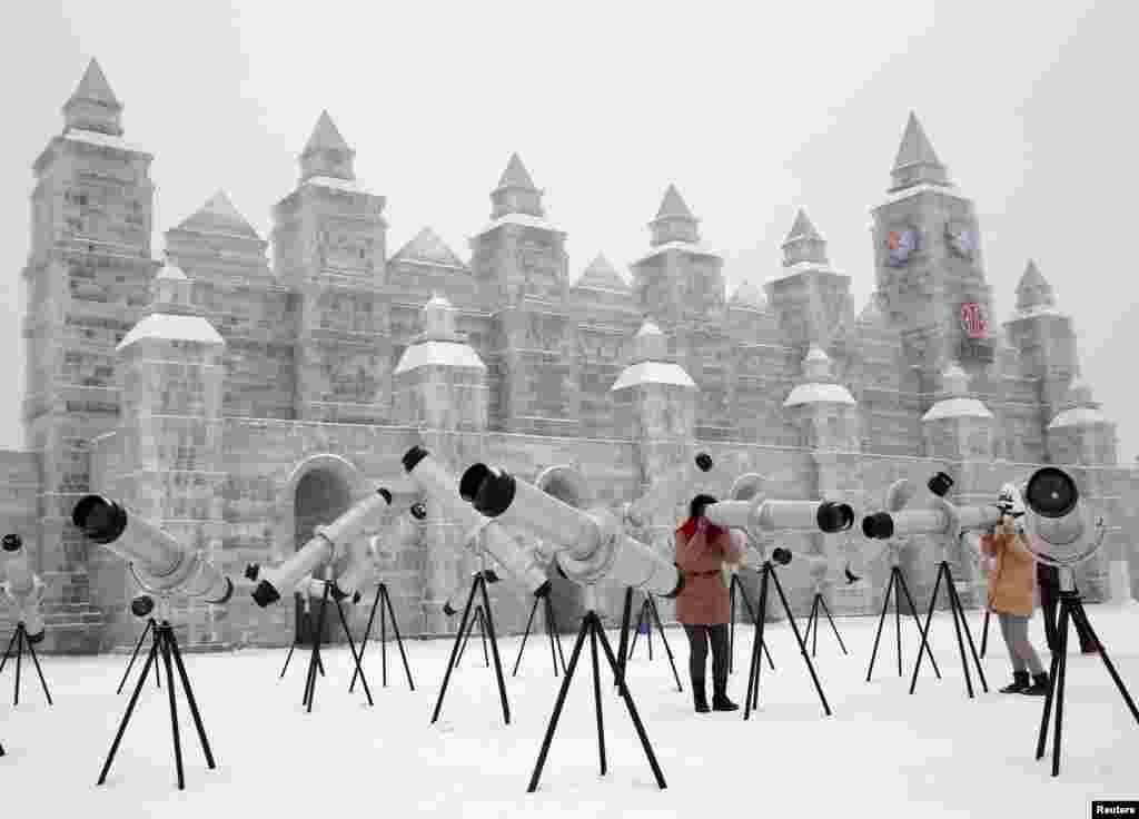 Pengunjung menggunakan kaleidoskop yang dipajang bersama patung es untuk Festival Es dan Salju Internasinal Harbin ke-31 di kota Harbin utara, provinsi province, China.