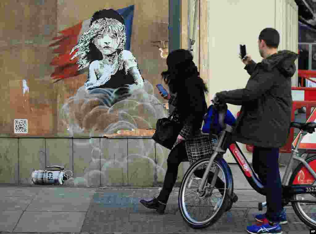 په لندن کې د فرانسې د سفارت په دیوال د نامتو بریتانیایي انځورګر، بنسکي، اثر چې خلک ترې عکس اخلي.