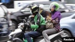 Seorang perempuan menggunakan transportasi online Go-Jek di Jakarta, 5 Desember 2015.