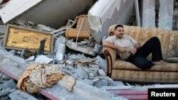 Người Palestine nằm giữa đống đổ nát của căn nhà bị phá hủy trong khu phố Shejaia sau các vụ pháo kích của Israel vào thành phố Gaza.