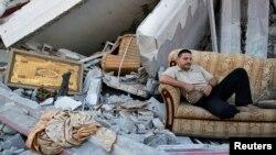 Một người dân Palestine ngồi giữa đống đổ nát của những căn nhà trong khu Shejaia, thành phố Gaza bị phá hủy nặng nề, theo nhân chứng, vì trúng pháo và không kích từ phía Israel.