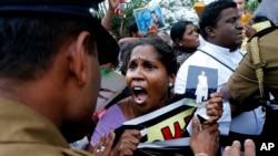 2013年11月15日,在斯里兰卡北部的贾夫纳公共图书馆外面举行示威抗议的少数族裔泰米尔人。当时英国首相卡梅伦正在图书馆内和泰米尔族领导人进行会谈。