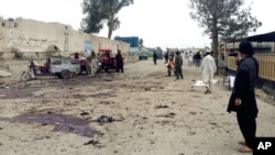 Afghan men inspect the site of a suicide attack in Khost city, Afghanistan, April 2, 2015.