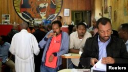 Customers drink coffee as they read newspapers at the Tamoka coffee bar in Ethiopia's capital Addis Ababa, Sept. 16, 2013.