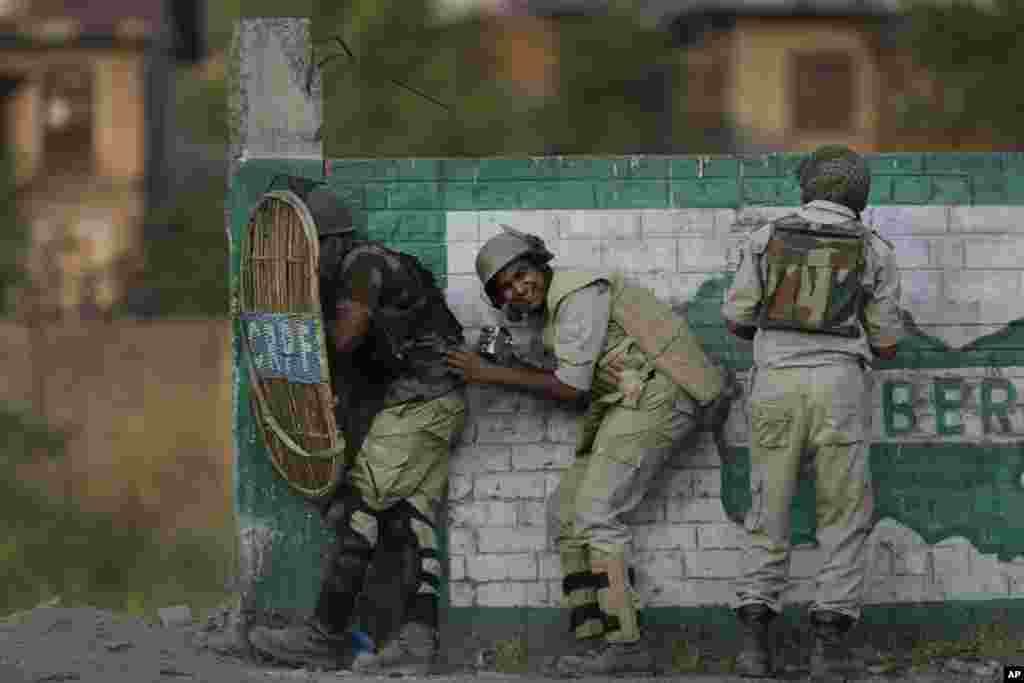 Indian paramilitary soldiers take shelter during clashes with Kashmiri stone throwers in Srinagar, Indian-controlled Kashmir.