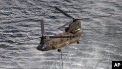 直升機在用水斗從海中取水,向福島核電站潑水