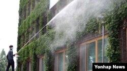 南韓光州一名男子在高溫天氣下向大廈外牆灑水降溫。