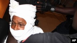FILE - Security personnel surround former Chadian dictator Hissene Habre inside the court, in Dakar, Senegal, July 20, 2015.
