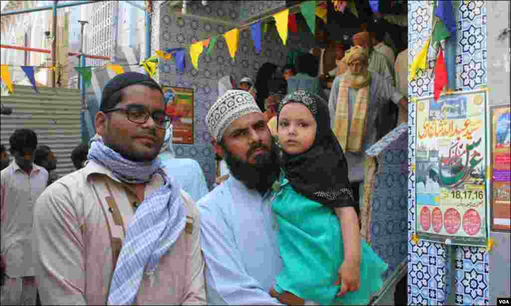 مزار پر آنے والے لاکھوں حاضرین میں شامل ایک بچی اپنے والد کی گود میں