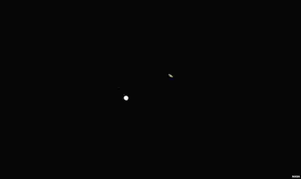 """Jupiter, left, and Saturn, right, are seen during the """"great conjunction"""" where the two planets appear a tenth of a degree apart from one another, Dec. 21, 2020, near Chapel Hill, North Carolina."""