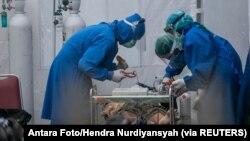 Medicinski radnici liječe osobu koja boluje od Covida.