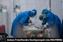 Petugas kesehatan merawat pasien COVID-19 di tenda darurat RS Sardjito saat terjadi kelangkaan oksigen di Sleman, Yogyakarta, 4 Juli 2021. (Foto: Antara Foto/Hendra Nurdiyansyah via REUTERS)