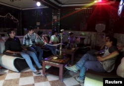 FILE - Afghan youths smoke shisha at a basement karaoke club in Mazar-i-Sharif June 1, 2015. Mazar-i-Sharif, the capital of Balkh province, is widely seen as one of a few oases of calm in the war-torn country.