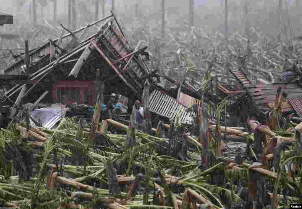 Para korban berdiri di luar rumah mereka yang musnah karena Topan Bopha di New Bataan, Compostela Valley (7/12).