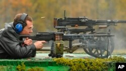 FILE - Russian Prime Minister Dmitry Medvedev shoots as he visits a factory, producing weapons components in Klimovsk outside Moscow on Wednesday, Oct. 3, 2012.