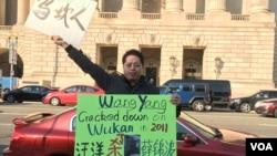 2016年11月23日,乌坎维权领袖庄烈宏在美中商贸联委会第27次会议的会场外手举抗议标语牌(美国之音莫雨拍摄)
