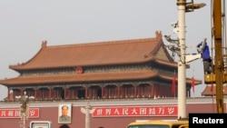 Seorang pria tengah memperbaiki kamera keamanan yang dipasang di Lapangan Tiananmen, Beijing (31/10).