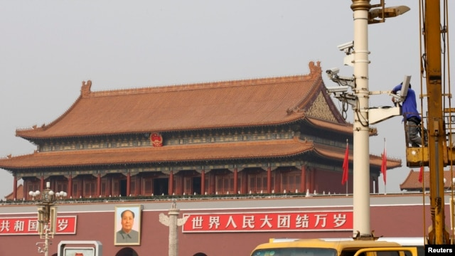A man works on a security camera which is installed at the Tiananmen square in Beijing October 31, 2013.