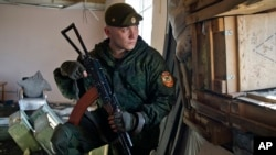 Một quân ly khai được Nga hậu thuẫn nhìn về hướng lực lượng chính phủ Ukraine từ cửa sổ tại một căn cứ ở ngoại ô Donetsk, Ukraine, 8/3/2015.