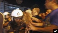 ພວກປະທ້ວງຕໍ່ຕ້ານແຜນການປະຢັດມັດທະຍັດເສດຖະກິດຂອງກຣີສ ຊຸກຍູ້ຕໍາຫລວດອອກ ຢູ່ນອກຕຶກລັດຖະສະພາກຣີສ ທີ່ກຸງ Athens. ວັນທີ 18 ກັນຍາ, 2011.