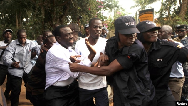 FILE - Ugandan policemen arrest opposition leader Kizza Besigye (front L) ahead of a rally to demonstrate against corruption and economic hardships in Uganda's capital Kampala, Jan. 19, 2012.