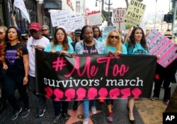 FILE - Participants march against sexual assault and harassment at the #MeToo March in the Hollywood section of Los Angeles on Nov. 12, 2017.