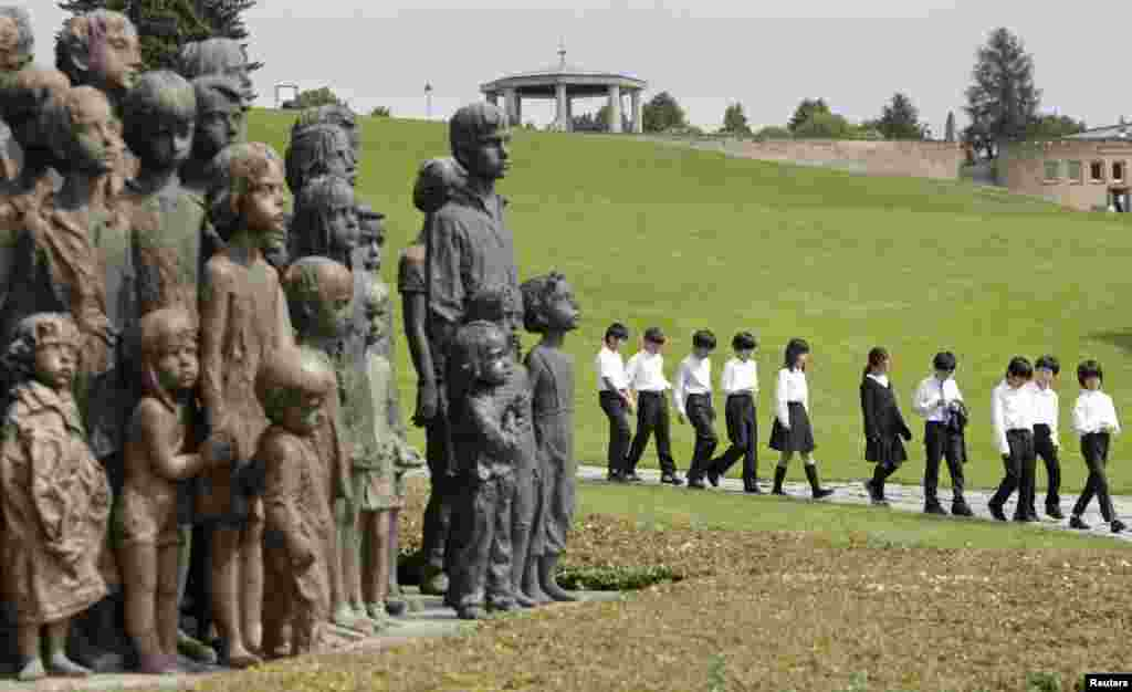 "Children arrive to pay their respects at the Lidice Memorial during a remembrance ceremony honoring the 71st anniversary of the destruction of Lidice village by Germans forces, in the Czech Republic. In 1942, German troops destroyed the village in retaliation for the assassination of Reinhard Heydrich, Nazi ""protector"" of Bohemia and Moravia, by Czech resistance fighters."