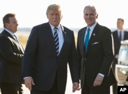 President Donald Trump stands on the tarmac with South Carolina Gov. Henry McMaster as he arrives on Air Force One at Greenville Spartanburg International Airport, in Greer, S.C., Monday, Oct. 16, 2017.