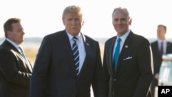 President Donald Trump stands on the tarmac with South Carolina Gov. Henry McMaster as he arrives on Air Force One at Greenville Spartanburg International Airport, in Greer, S.C., Monday, Oct. 16, 2017, en route Greenville, S.C., for a fundraiser for McMaster.