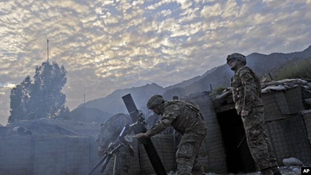US army soldiers fire mortar rounds towards insurgent positions at Outpost Monti in Kunar province, September 17, 2011.