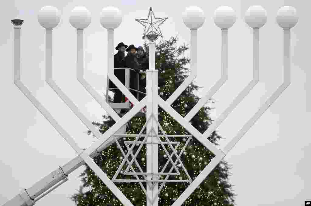 Rabbis install a giant Hanukkah Menorah for the eight-day Jewish Festival of Lights, named Hanukkah, in front of a Christmas tree at the Brandenburg Gate in Berlin, Germany.