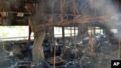 Seorang polisi menginspeksi kereta api yang hangus terbakar di Kothacheruvu, 155 kilometer sebelah utara Bangalore, India (28/12).
