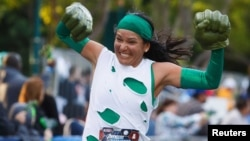 FILE - Maxine Cunningham pumps her Thing character's fists after completing the Avengers Super Heroes Half Marathon in and around the Disney Parks in Anaheim, California, Nov. 16, 2014.