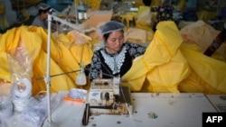 Una mujer trabaja en la elaboración de trajes protectores contra el ébola en Beijín.