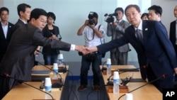 Kim Kiwoong (kanan), pimpinan delegasi Korea Selatan berjabat tangan dengan Park Chol Su pimpinan delegasi dari Korea Utara dalam rapat di Komite Manajemen Kawasan Industri Kaesong di Korea Utara (17/7).
