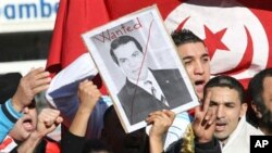 A woman holds a picture of Tunisia's deposed leader Zine El Abidine Ben Ali, reading 'Wanted', during a demonstration showing solidarity with Tunisians, in Marseilles, France , Jan. 15, 2011