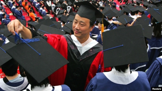 A man adjusts a student's mortar board during the graduation ceremony at Fudan University in Shanghai June 28, 2006. (File)
