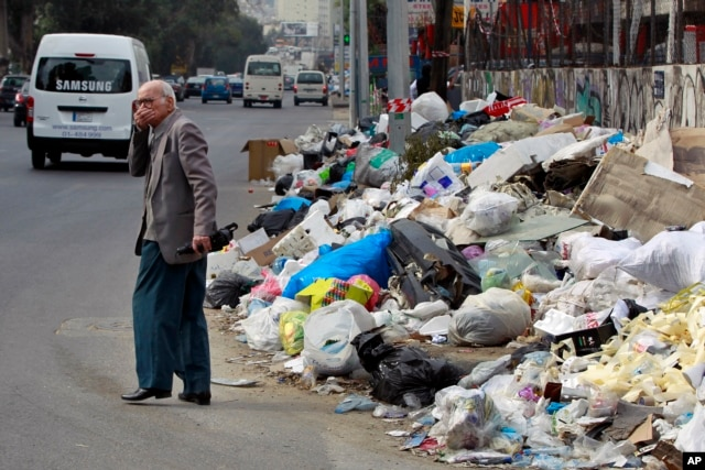 A Lebanese man covers his nose from the smell as he passes by a pile of garbage on a street in Beirut, Dec. 17, 2015.