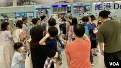 在香港国安法实施满一周年之际,香港民众在机场离境时与家人挥手道别(美國之音 / 湯惠芸)