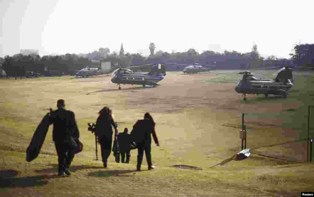 Members of the White House travelling staff walk to a group of helicopters about to transport U.S. President Barack Obama from a soccer field in Johannesburg, June 29, 2013.