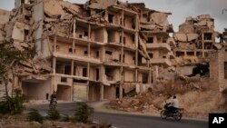 FILE - Motorcycles ride past buildings destroyed during the fighting in the northern town of Ariha, in Idlib province, Syria, Sept. 20, 2018.