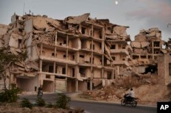 In this Sept. 20, 2018 photo, motor cycles ride past buildings destroyed during the fighting in the northern town of Ariha, in Idlib province, Syria.