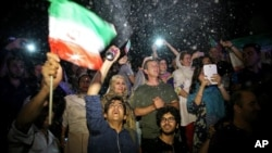 FILE - A group of jubilant Iranians cheer and spray artificial snow during street celebrations following the announcement of a landmark nuclear deal, in Tehran, July 14, 2015.